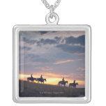 Jinetes de lomo de caballo en la puesta del sol 2 colgante cuadrado