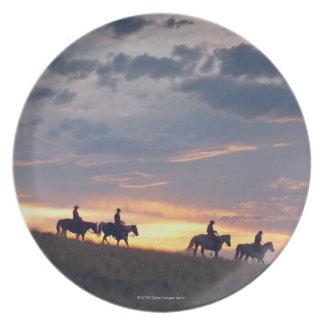 Jinetes de lomo de caballo en la puesta del sol 2 plato de cena