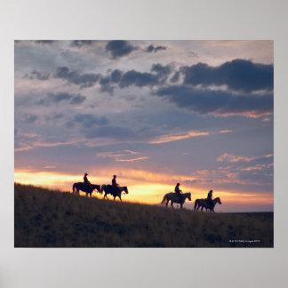 Jinetes de lomo de caballo en la puesta del sol 2 póster