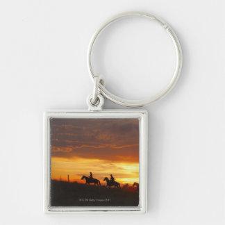Jinetes de lomo de caballo en la puesta del sol llavero cuadrado plateado
