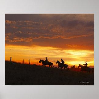 Jinetes de lomo de caballo en la puesta del sol póster