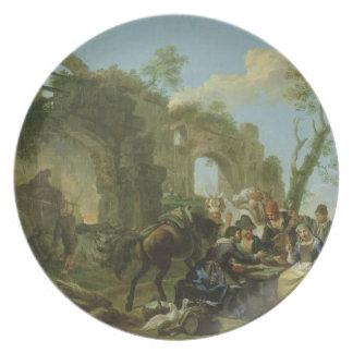 Jinetes que descansan entre ruinas clásicas con un plato de cena