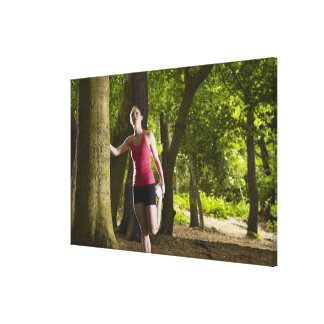 Jogger stretching in forest stretched canvas print