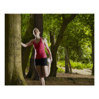 Jogger stretching in forest poster
