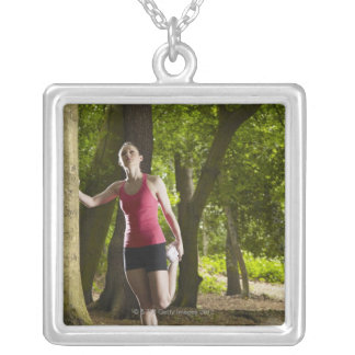 Jogger stretching in forest square pendant necklace