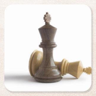 Juego de ajedrez encima posavasos de cartón cuadrado