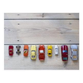 Juegue los coches alineados en una fila en piso postales