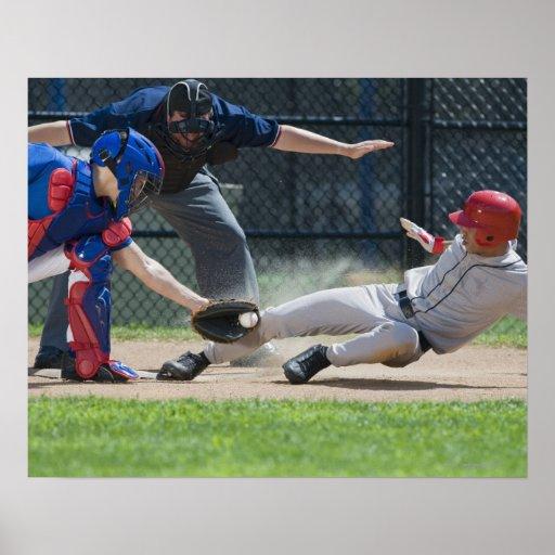 Jugador de béisbol que resbala dentro de la meta posters