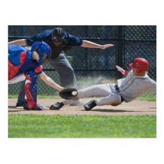 Jugador de béisbol que resbala dentro de la meta postales