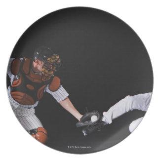 Jugador de béisbol que resbala dentro de una base plato para fiesta