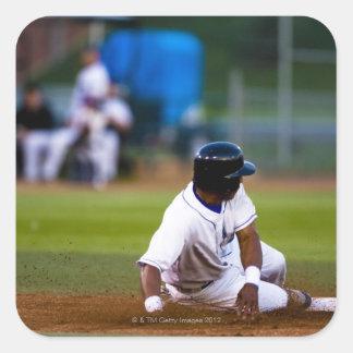Jugador de béisbol que resbala sobre una base colcomania cuadrada