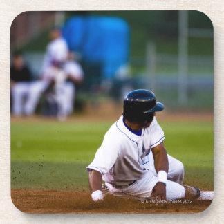 Jugador de béisbol que resbala sobre una base posavaso