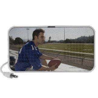 Jugador de fútbol americano que se sienta en blanq portátil altavoces