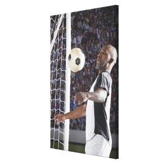 Jugador de fútbol que hace frente a la bola del me lienzo envuelto para galerías