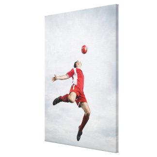 Jugador de fútbol y balón de fútbol en mediados de impresion de lienzo
