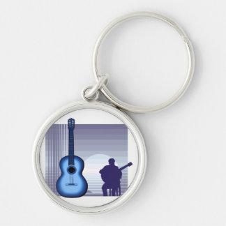 jugador de la guitarra acústica que sienta bluish. llavero redondo plateado