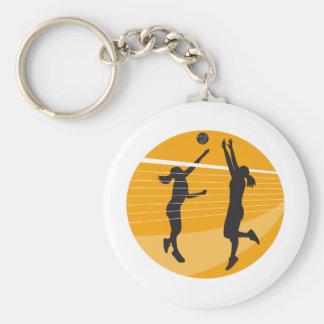 Jugador de voleibol que clava bloqueando la bola i llaveros