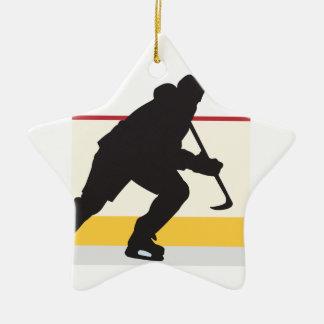 jugador del hockey sobre hielo en el movimiento adorno navideño de cerámica en forma de estrella