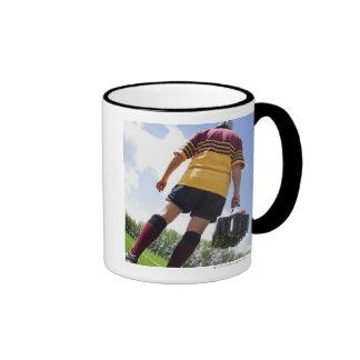 Jugador del rugbi en la línea lateral con los taza de dos colores