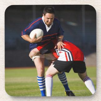 Jugador del rugbi que aborda otro posavaso