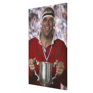 Jugador del rugbi que celebra la taza del trofeo,  lona envuelta para galerías