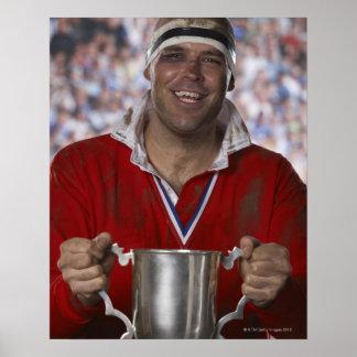 Jugador del rugbi que celebra la taza del trofeo, póster