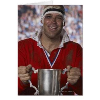 Jugador del rugbi que celebra la taza del trofeo,  tarjetas