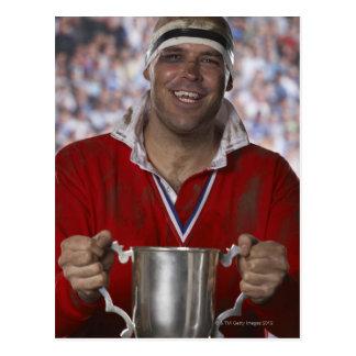 Jugador del rugbi que celebra la taza del trofeo, postal