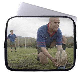 Jugador del rugbi que coloca la bola en echada del manga portátil