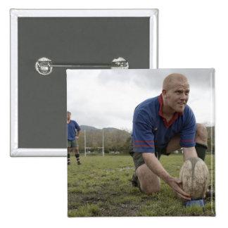 Jugador del rugbi que coloca la bola en echada del pin cuadrado