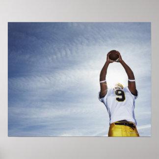 jugador del rugbi que detiene la bola con el cuerp póster