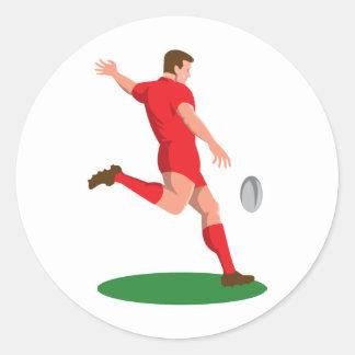 jugador del rugbi que golpea la bola con el pie etiqueta redonda