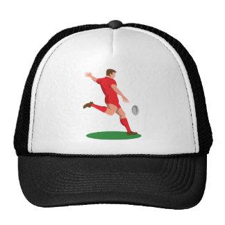 jugador del rugbi que golpea la bola con el pie re gorro de camionero