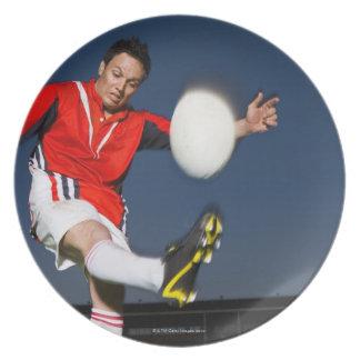 Jugador que golpea la bola con el pie plato de cena