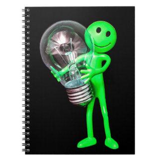 Juguete extranjero verde que sostiene un cuaderno
