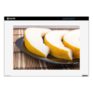Juicy yellow melon on wooden background laptop skins
