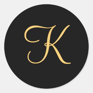 k inicial Oro-coloreada en el pegatina negro del