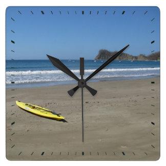 Kajak en la playa reloj cuadrado