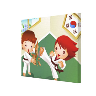 Karate boy holding wood with another breaking it canvas print