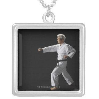 Karate master demonstrating, studio shot silver plated necklace