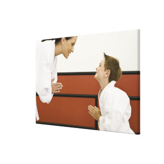 Karate teacher and boy (4-5 years) bowing to canvas print