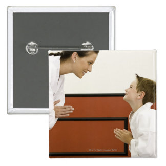 Karate teacher and boy (4-5 years) bowing to pinback button