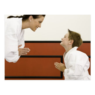 Karate teacher and boy (4-5 years) bowing to post cards