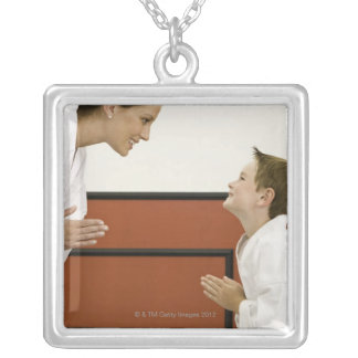 Karate teacher and boy (4-5 years) bowing to silver plated necklace