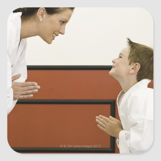 Karate teacher and boy (4-5 years) bowing to square sticker