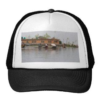 Kashmiri man rowing a shikara with people in it trucker hat