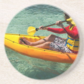 Kayaker paddling in clear water drink coaster