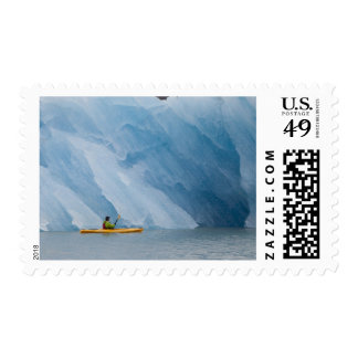 Kayaker pauses to look at a magnificent iceberg postage stamp