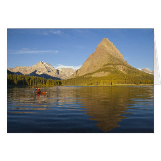 Kayaking in Swiftcurrent Lake at sunrise in the Card
