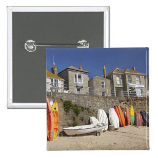 Kayaks and dinghies stacked against seawall at pinback buttons